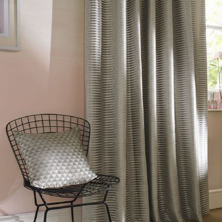 Ashley Wilde -  Axel Fabric Collection - Horizontally streaked dark and light grey curtains with a grey and white triangle print cushion on a black mesh chair