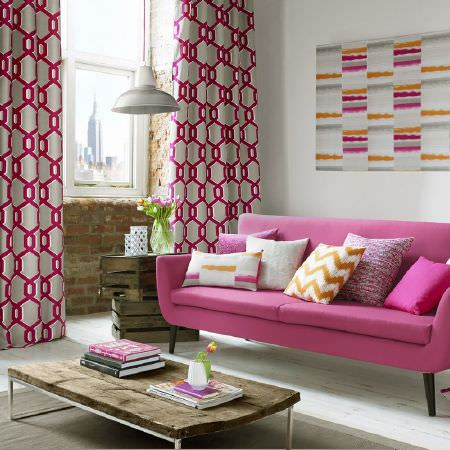 Ashley Wilde -  Blake Fabric Collection - A hot pink sofa with pink and silver geometric print curtains, pink, white and orange cushions and art, and a low table