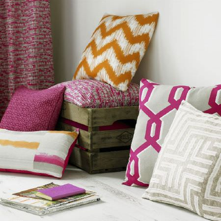 Ashley Wilde -  Blake Fabric Collection - Pink, grey, white and orange patterned scatter cushions stacked in and around a wooden crate, with pink speckled curtains