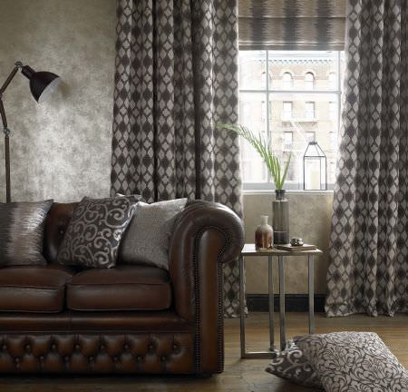 Ashley Wilde -  Camara Fabric Collection - Modern leather sofa covered with a collection of elegant cushions and a beige curtain with brown geometric pattern