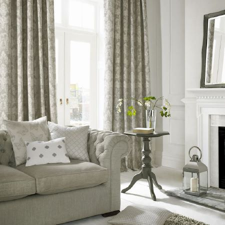 Ashley Wilde -  Coastal Fabric Collection - Plain grey sofa with grey patterned curtains, white and grey patterned cushions, a grey wood side table, grey framed mirror and grey lantern