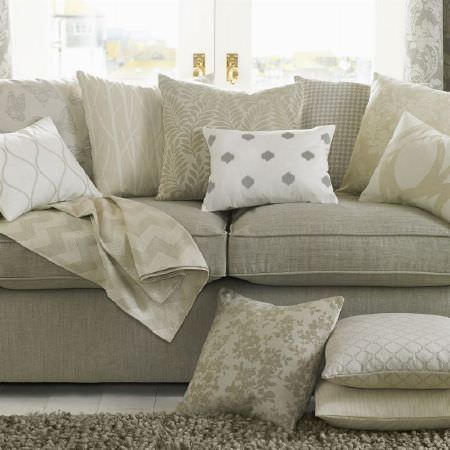 Ashley Wilde -  Coastal Fabric Collection - Grey sofa with fluffy grey rug and scatter cushions in grey, white and cream floral, leaf, butterfly, lined and geometric print designs