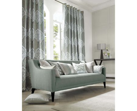 Ashley Wilde -  Coniston Fabric Collection - Elegant curtains decorated with big luxurious pattern in white and a plain sofa covered with modern cushions