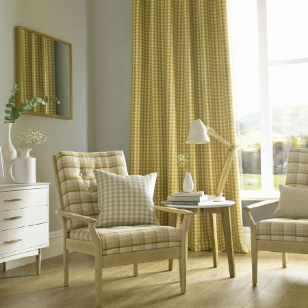 Ashley Wilde -  Edderton Fabric Collection - Pale wood framed armchairs with mustard yellow and beige checked cushions, with yellow-green checked curtains, chest of drawers, table, lamp