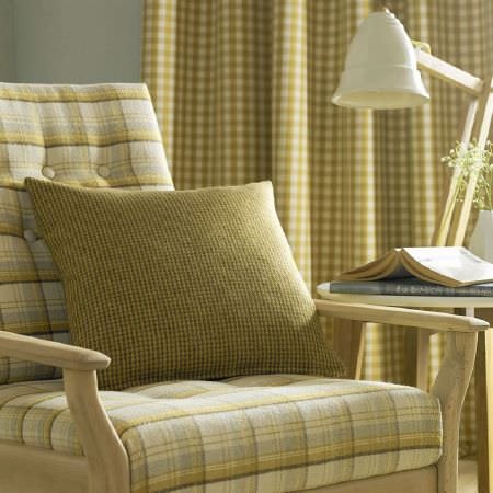 Ashley Wilde -  Edderton Fabric Collection - Mustard yellow, grey and white checks (in different sizes) on curtains, scatter cushions and armchair seat cushions, with wood table and lamp