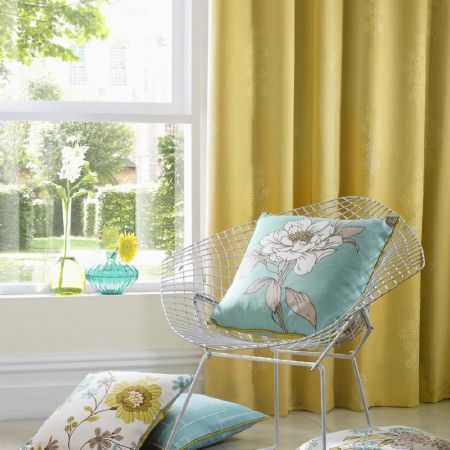Ashley Wilde -  Eden Fabric Collection - Yellow curtain with faint floral impressions behind a chair with a turquoise and a white cushion with classic flower decorations