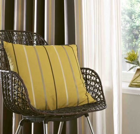 Ashley Wilde -  Edina Fabric Collection - Yellow cushion decorated with a pattern of thin stripes and a matching stripe pattern on a curtain