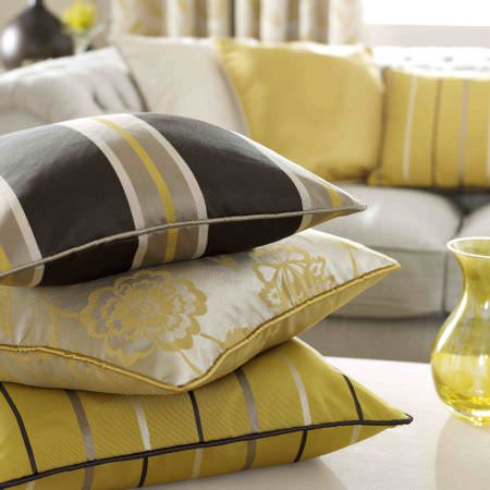Ashley Wilde -  Edina Fabric Collection - Silky silver cushion with gold floral pattern and dark grey and yellow cushions featuring stripe designs