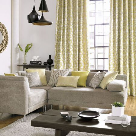 Ashley Wilde -  Emeka Fabric Collection - Grey corner seat sofa with grey, white and green cushions, patterned green and white curtains, pale grey rug, black lights and wooden table