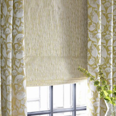 Ashley Wilde -  Emeka Fabric Collection - Olive green curtains featuring a white leaf print, alongside window blinds with irregular grey, white and green dashed lines