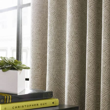 Ashley Wilde -  Emeka Fabric Collection - Curtains covered in a series of concentric beige-grey and cream circles, all overlapping each other