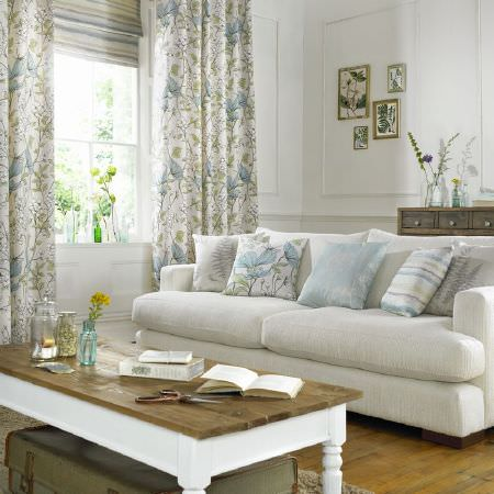 Ashley Wilde -  Fleur Fabric Collection - White coffee table with brown wood top, white sofa, blue and white floral curtains, white and blue cushions, dark grey chest, and glass vase