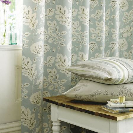 Ashley Wilde -  Fleur Fabric Collection - Assorted white leaves printed on blue fabric, with a cream, blue, green striped cushion, a cream and grey floral cushion and a wooden table