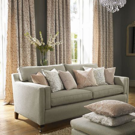 Ashley Wilde -  Kensington Fabric Collection - Light grey sofa and footstool with patterned cushions in light grey and cream-beige shades, with curtains and a chandelier