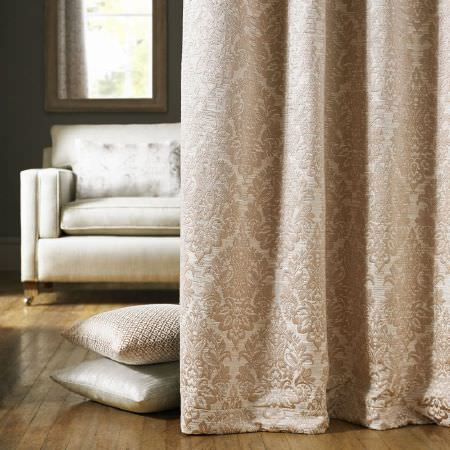 Ashley Wilde -  Kensington Fabric Collection - Ornately patterned cream-beige and white curtains in front of a white sofa and two very pale coloured scatter cushions