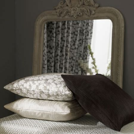 Ashley Wilde -  Kensington Fabric Collection - A large grey framed mirror with a black cushion, two silver and white patterned cushions, and a silver and white footstool
