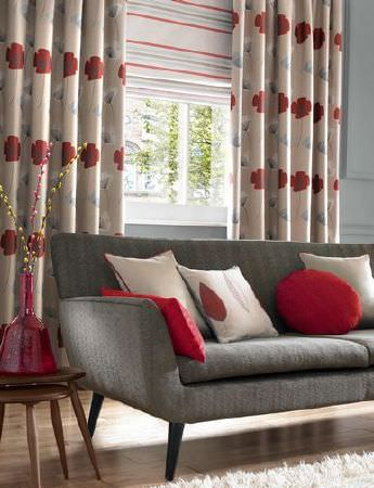 Ashley Wilde -  Loretta Fabric Collection - A classic but modern grey upholstered couch with plain red and white pillows, in front of a sandy curtain with a red modern flower pattern