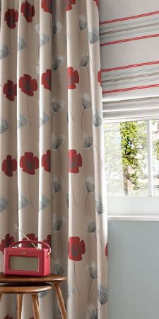 Ashley Wilde -  Loretta Fabric Collection - White roman blind with red and blue horizontal stripes behind a modern sandy curtain with red flowers and white dandelions
