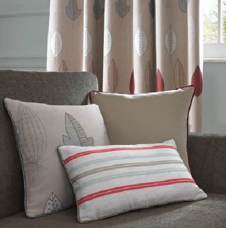 Ashley Wilde -  Loretta Fabric Collection - A beige curtain with a simple modern leaf pattern, behind a grey upholstered couch with a striped, plain and  leaf decorated cushions