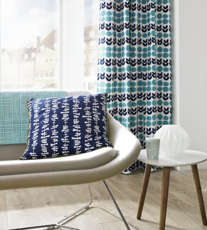 Ashley Wilde -  Lotta Jansdotter Signature Fabric Collection - Stylised navy blue tulips with dusky blue circles printed on white curtains, with a blue and white cushion on a white sofa