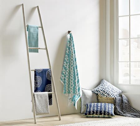 Ashley Wilde -  Lotta Jansdotter Signature Fabric Collection - A white ladder draped with three folds of white, navy blue and dusky blue fabrics, with cushions and fabrics in a basket