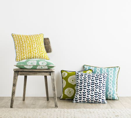 Ashley Wilde -  Lotta Jansdotter Signature Fabric Collection - A rustic wooden chair with four patterned scatter cushions in yellow, mint green, olive green, sky blue, navy and white