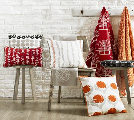 Ashley Wilde -  Lotta Jansdotter Signature Fabric Collection - Red, orange, black, white and grey making up folds and swathes of patterned fabric as well as cushions on a wooden chair