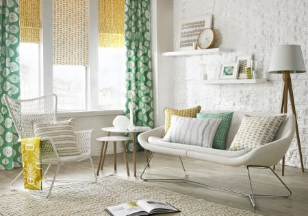 Ashley Wilde -  Lotta Jansdotter Signature Fabric Collection - A white sofa, tables and floor lamp, with patterned cushions, curtains, blinds and fabric in white, mint green and citrus