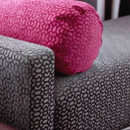 Ashley Wilde -  Malone Fabric Collection - A close-up photo of a pink cylindrical cushion and a grey upholstered couch, both with a modern pattern