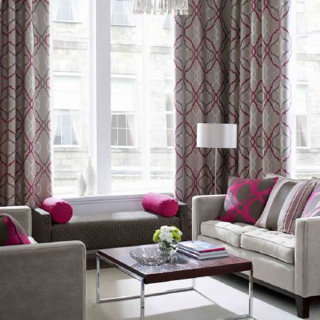Ashley Wilde -  Malone Fabric Collection - White and grey upholstered couches with square and cylindrical pillows in front of silver grey curtains with a modern purple circle pattern