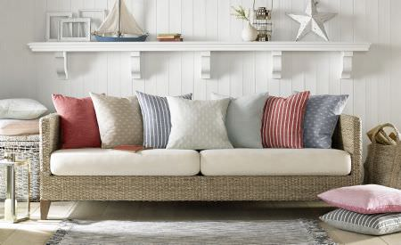 Ashley Wilde -  Newport Fabric Collection - A square wicker woven sofa with plain white seat cushions and scatter cushions in cool white, blue, red and pink shades