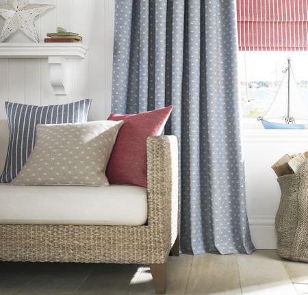 Ashley Wilde -  Newport Fabric Collection - Plain, striped and star print curtains and cushions in blue, pale grey and red, on a wicker woven sofa with white seats