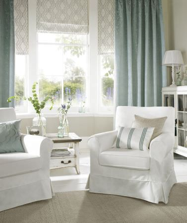 Ashley Wilde -  Oldbury Fabric Collection - Plain white fabric armchairs with striped and plain cushions and curtains in pale grey and duck egg blue, with white tables