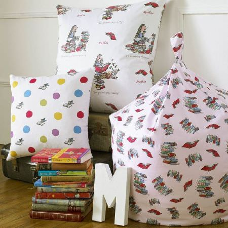 Ashley Wilde -  Roald Dahl Fabric Collection - Pink beanbag with pattern of stacks of books, Roald Dahl character-covered cushion, cushion with polka dots and books, briefcase, wooden