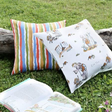 Ashley Wilde -  Roald Dahl Fabric Collection - Unevenly striped cushion in red, blue, white, green, gold and brown, with a white cushion scattered with human and animal characters