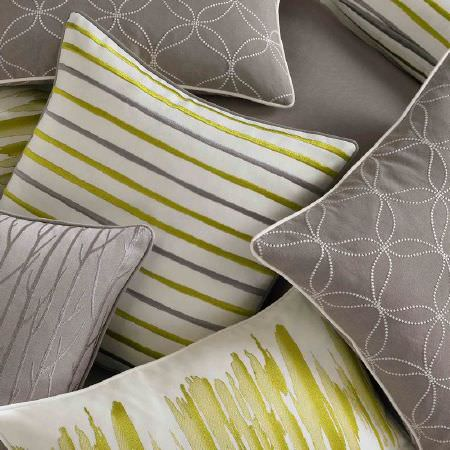 Ashley Wilde -  Serene Fabric Collection - Grey cushions with dotted circles and wavy lines and white edging, and white cushions with lime green stripes and green brushstrokes
