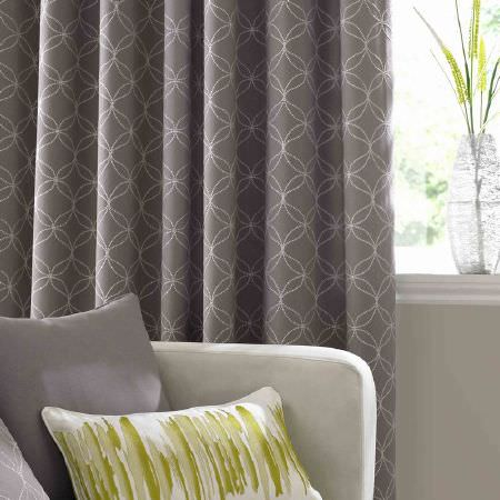 Ashley Wilde -  Serene Fabric Collection - Classic grey curtain with white dotted circles and a white uphosltered couch with plain grey and brushstroke decorated cushions