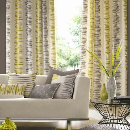 Ashley Wilde -  Serene Fabric Collection - Grand white curtains with grey and green brushstroke bands behind a white modern couch with plain, striped and patterned cushions