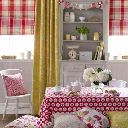 Ashley Wilde -  Summersdale Fabric Collection - Red and white tartan roman blinds with a yellow floral curtain, a red tablecloth decorated with white spots with fruits, and red cushions