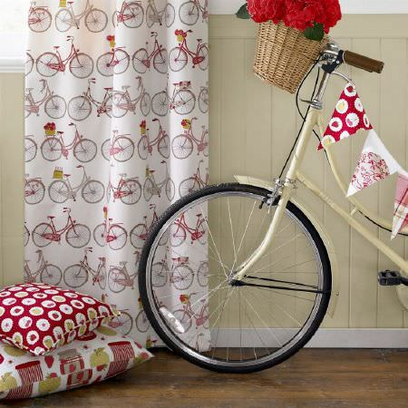 Ashley Wilde -  Summersdale Fabric Collection - White curtain printed with old bicycles, red cushions decorated with fruits and marmalade jars, and an old bike with red bunting