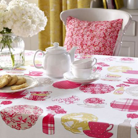 Ashley Wilde -  Summersdale Fabric Collection - White tablecloth with prints of dishes, teapots and flowers, and a red pillow with small pink flowers for a country house style