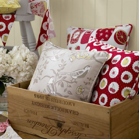Ashley Wilde -  Summersdale Fabric Collection - A box of cushions, with a grey cushion with birds, a red pillow with fruits, and a cushion decorated with marmalades, and bunting on wall