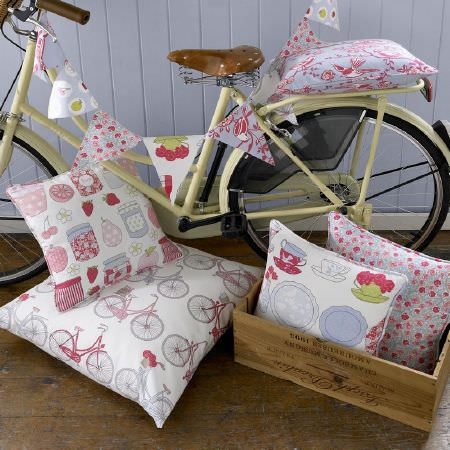 Ashley Wilde -  Summersdale Fabric Collection - Cushions decorated with bicycles, marmalade jars and dishes, next to a bicycle with bunting for a country house