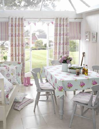Ashley Wilde -  Thornbury Fabric Collection - A country style house with a blue tablecloth with pink roses, an upholstered bench pad with cushions, and white curtains with flowers