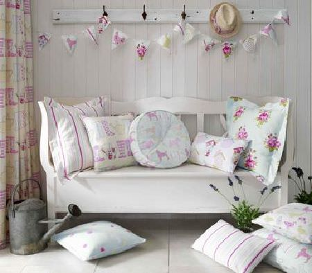 Ashley Wilde -  Thornbury Fabric Collection - A wooden bench with round and rectangular cushions, with pink roses, dogs, and pink stripes, next to a white curtain with pink stripes