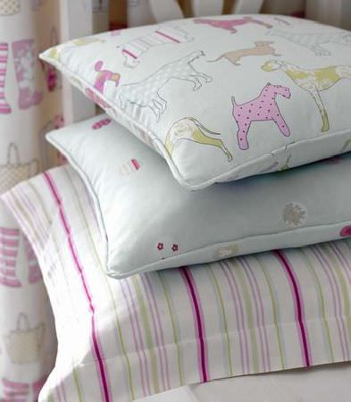 Ashley Wilde -  Thornbury Fabric Collection - Light blue cushions decorated with dogs and flowers, and white pink striped cushions, and a white curtain with wellies and watering pots