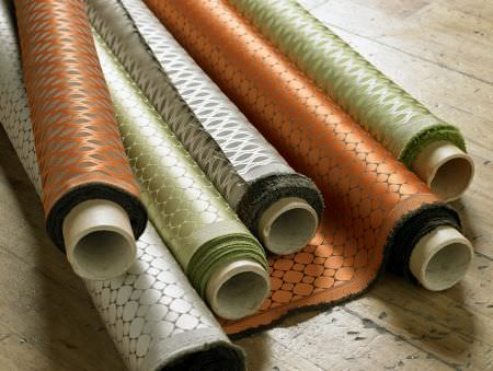 Ashley Wilde -  Vinci Fabric Collection - Foil printed burnt orange, light green and white fabrics with two small geometric prints, laid on the floor in rolls