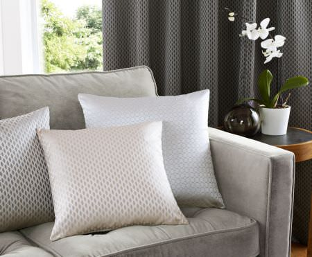 Ashley Wilde -  Vinci Fabric Collection - 3 cushions in subtly different shades of white, with very small patterns, on a grey fabric sofa with dark grey curtains
