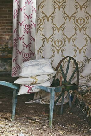 Barneby Gates -  Barneby Gates Fabric Collection - Vintage wheelbarrow with fabric and three cushions, all with an antler pattern on a cream background; one in silver, one gold and one red