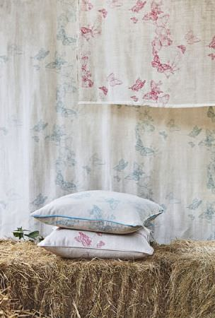 Barneby Gates -  Barneby Gates Fabric Collection - Pink and light blue butterflies arranged in circles over cream fabric, formed into two scatter cushions and a backdrop made of the two fabrics